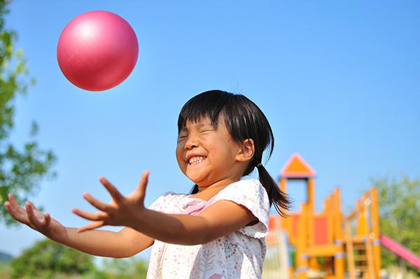 A imagem mostra uma criança jogando uma pequena bola rosa para cima. Ela sorri com os olhos fechados.