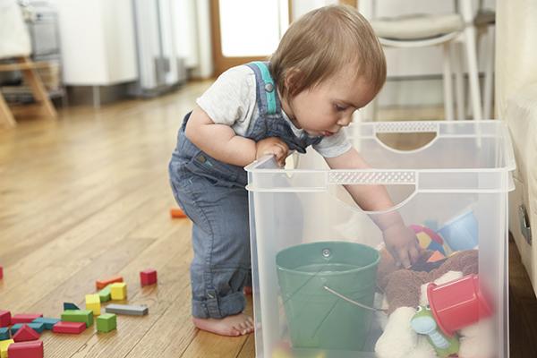 A imagem mostra uma criança pequena colocando a mão dentro de uma caixa de plástico transparente onde estão vários objetos