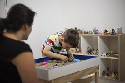 Na imagem há um garoto em uma sala brincando com objetos que estão dentro uma caixa de areia. Há o destaque de uma mulher de costas, olhando para ele.