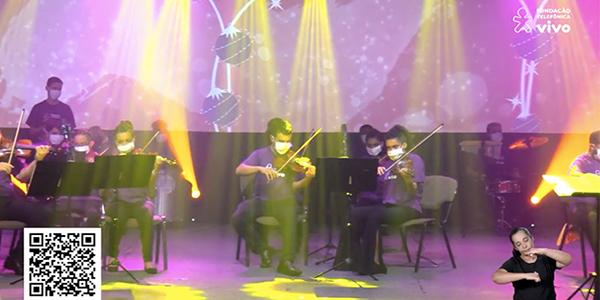 Imagem mostra jovens tocando violino durante o espetáculo Cantata de Natal. Todos estão em cima de um palco, usando máscara de proteção facial e camiseta roxa com logo da Vivo.