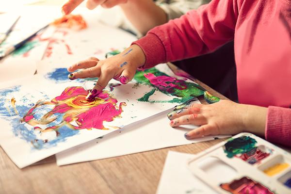 A imagem mostra as mãos de uma criança em destaque usando tinta para pintar com os dedos em uma folha de papel