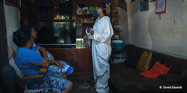 A imagem mostra uma voluntária de máscara e roupa de proteção branca dentro da casa de duas mulheres em Paraisópolis. Elas estão sentadas olhando para a voluntária que está de pé.