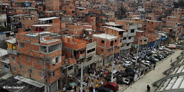 A imagem, vista de cima, mostra um grupo de pessoas andando pelas ruas de Paraisópolis. É possível ver várias casas e construções de tijolos.