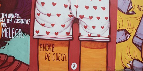 A imagem mostra detalhes do muro grafitado com o livro Menino Invísivel