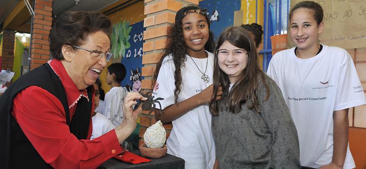 Professora Lea se diverte com três alunas em uma feira de ciências