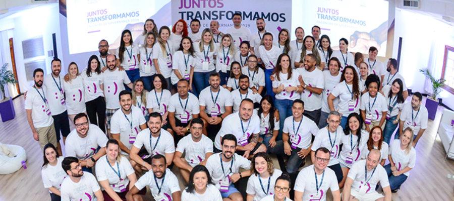 Colaboradores do Grupo Telefônica posam para foto em grupo utilizando a camiseta do Programa de Voluntariado. Atrás deles, há uma projeção em telão onde se lê: Juntos Transformamos
