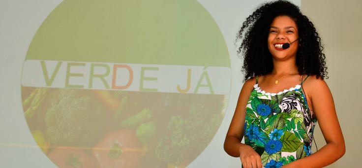 """Imagem mostra jovem em apresentação. No quadro atrás dela se lê """"Verde Já"""""""