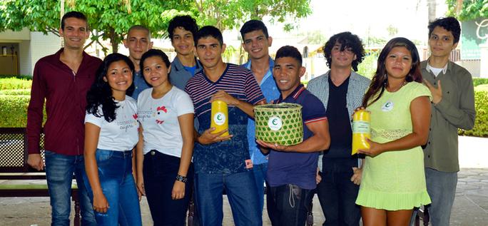 Imagem mostra grupo de pessoas posando para foto. Um dos jovens segura uma cesta verde e amarela.