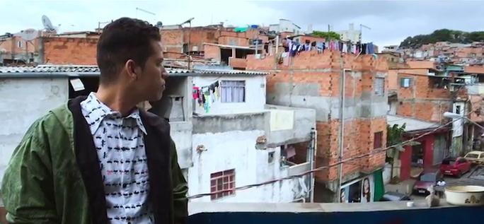 Rapaz está olhando para o horizonte na laje de uma comunidade.