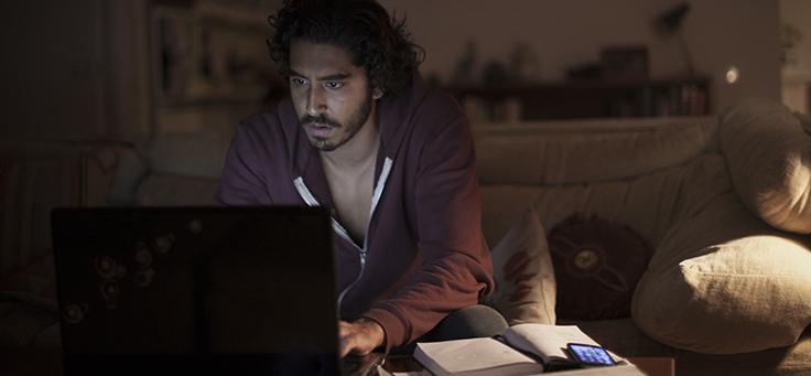 Imagem mostra o ator Dev Patel olhando para um computador em cena do filme Lion