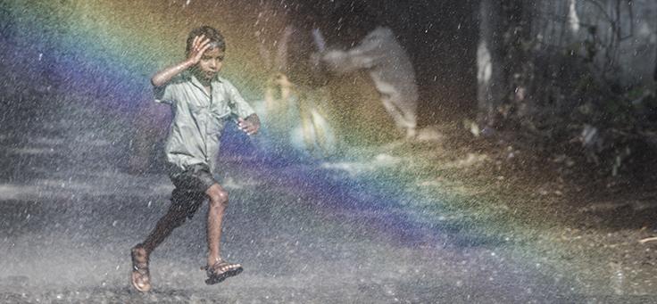 Cena do filme Lion mostra um menino correndo pela chuva e um arco-íris ao fundo