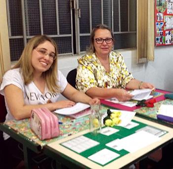 Educadora Rosângela Thomazino Mendes, à direita, sentada em mesa na escola EstadualProfessor Irineu Tobias