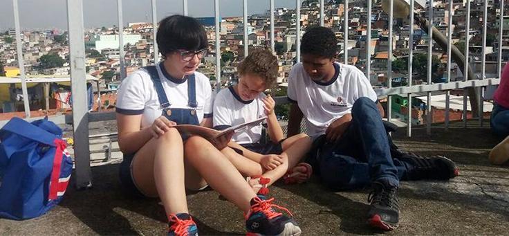 Três crianças aparecem sorrindo e lendo no pátio da escola