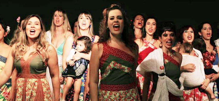 Grupo de mães cantam ao lado dos filhos