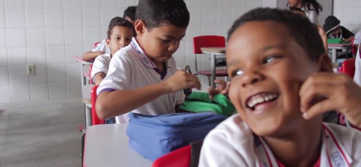 Imagem mostra frame do vídeo do projeto Aula Digital em Sergipe com crianças sorrindo em sala de aula