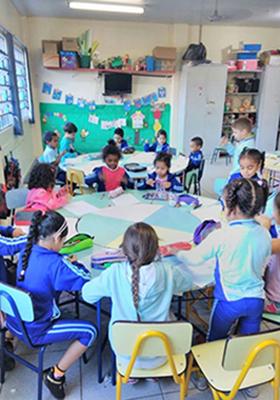 Imagem mostra crianças sentadas em roda na sala de aula