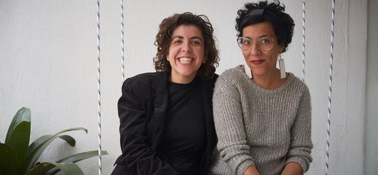 Duas mulheres, uma de cinza, uma de preto, lado a lado, posam para foto