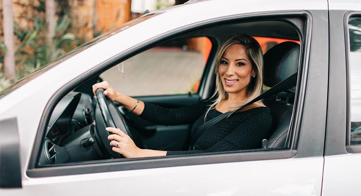 Mulher de cabelo loiro ao volante de carro tira foto de perfil