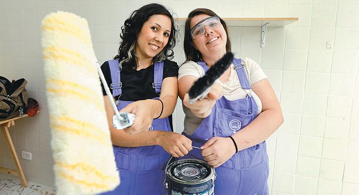 Duas mulheres de macacão jeans seguram rolo de tinta, pincel e balde