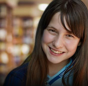 Menina falando na frente de estante de livros.