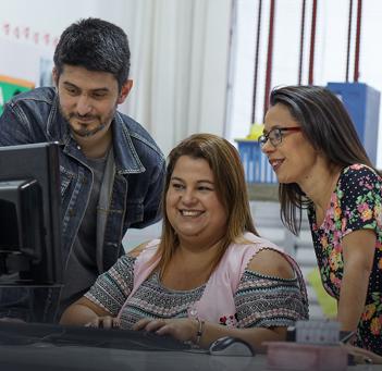 Professora em frente ao computador sorri. Ao seu lado um homem e uma mulher também olham para o computador.