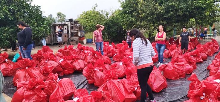 Dezenas de Sacolas com doações de voluntários da fundação telefônica vivo no chão para triagem