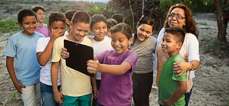 Em meio à natureza, quatro crianças sorriem encantadas, acompanham conteúdo em um tablet