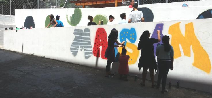 Crianças e adolescente fazem grafite em muro da escola