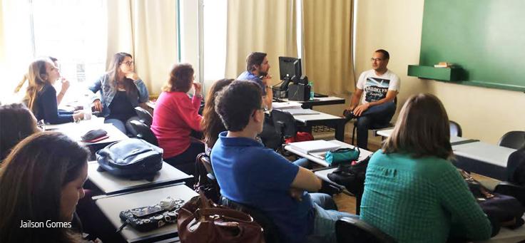 Professor está sentado em frente à lousa diante de sala cheia de alunos