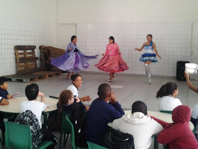 Três meninas com vestidos típicos fazem apresetação de dança boliviana em ginásio