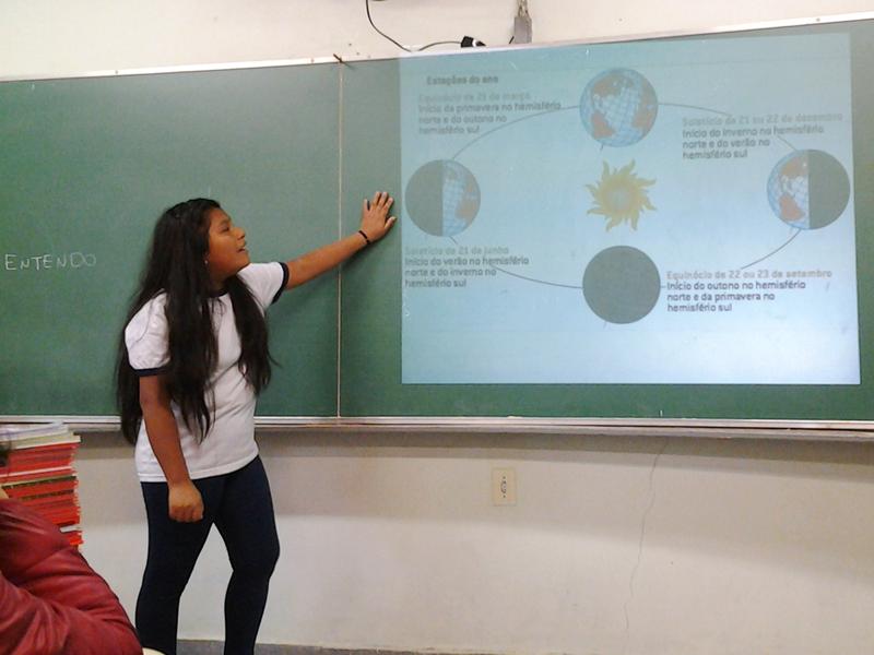 Menina de traços bolivianos com a mão apoiada na lousa olha para projeção enquanto faz apresetnação na sala de aula