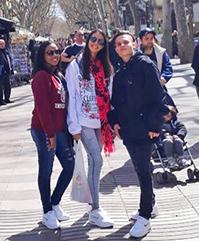 Duas meninas e um menino, na faixa de 16 anos, posam para foto em calçadão de Barcelona.