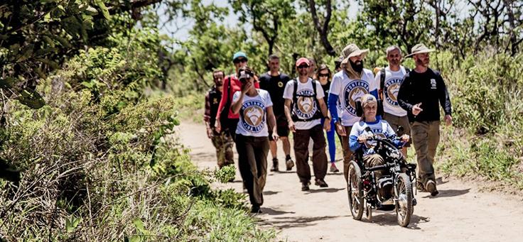 Juliana, usando a Julietti à frente de grupo de pessoas andam em trilha