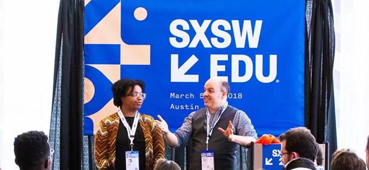 Imagem mostra duas pessoas à frente de um painel onde se lê SXSW Edu