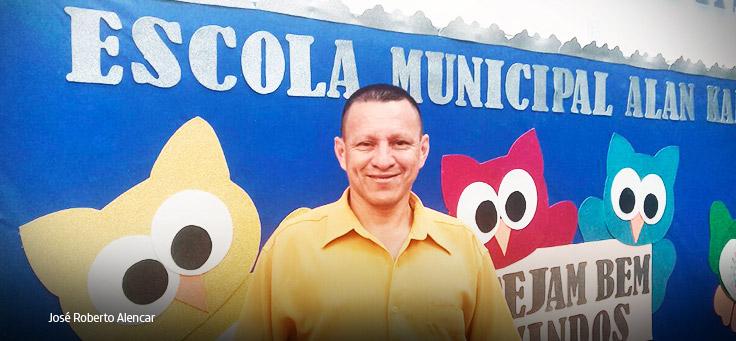 Homem de camisa amarela em frente a muro azul.