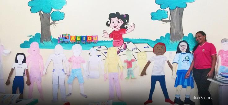 Professora de camiseta rosa posa em frente à parede com desenhos infantis