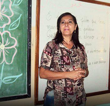 Professora está em frente a lousa onde há uma flor desenhada