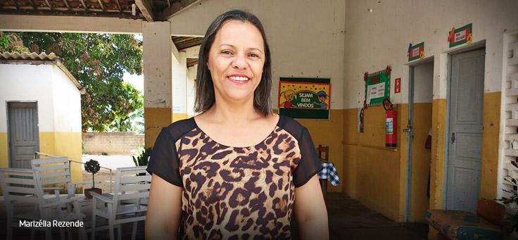 Marizélia dos Santos Rezende em frente à escola, de blusa rosa e calça jeans