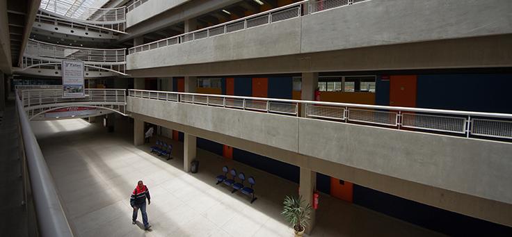 Texto Alternativo Imagem do pátio central da Fatec de Itaquera, na zona leste de São Paulo. Corredores centrais dão para o pátio. Estrutura de três andares do prédio é em concreto aparente, e claraboia deixa passar a luz refletida no chão