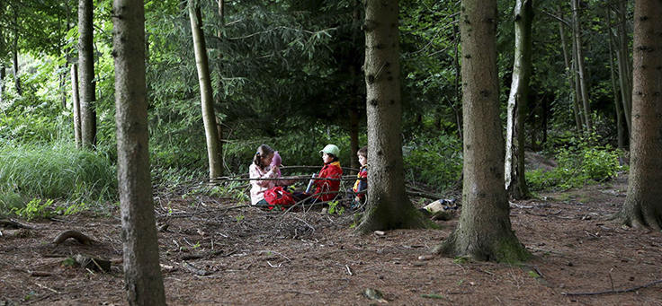 Três crianças brincam em meio a árvores em uma floresta na Alemanha.