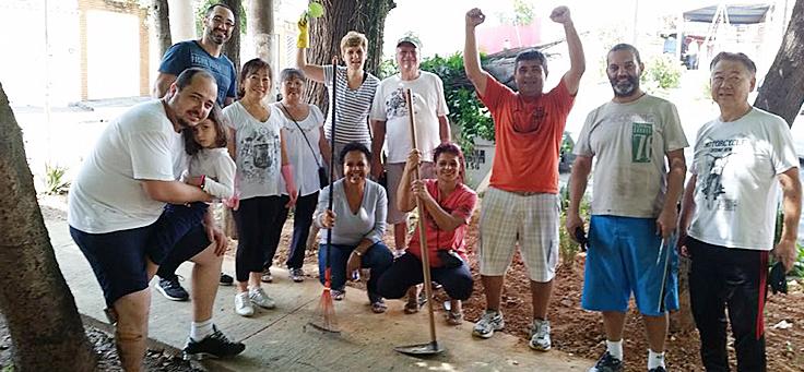 De camiseta laranja, Zacarias aparece com os braços levantados ao lado de outras pessoas voluntárias