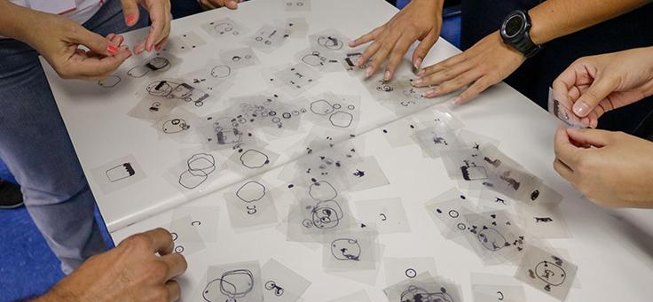 Imagem mostra pessoas mexendo em pequenos papeis sobre uma mesa