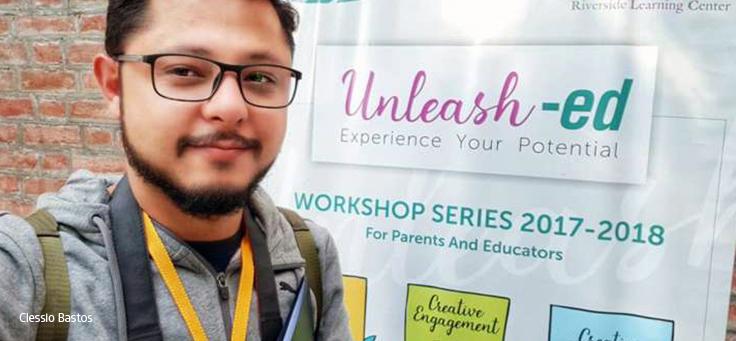 "Rapaz de óculos sorri em frente a banner onde se lê ""Unleash-Ed – Explore your Potential"""