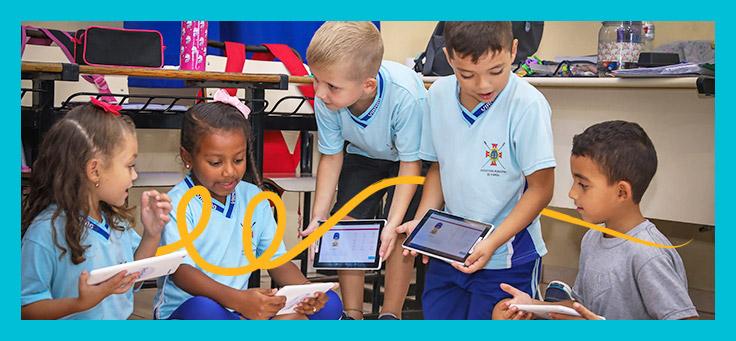 Imagem mostra grupo de crianças segurando tablets e conversando. Algumas estão em pé e outras sentadas.