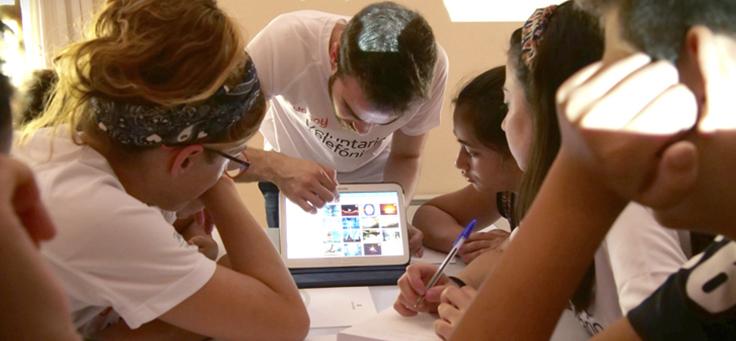 Homem usando camiseta do programa de voluntariado do Grupo Telefônica Vivo mostra tablete a jovens