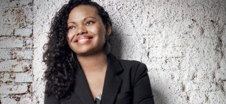 Foto mostra Adriana Barbosa, fundadora da Feira Preta, usando terno e sorrindo