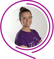 Maria Tereza, do Programa de Voluntariado da Fundação Telefônica Vivo, usa camiseta púrpura, tem o cabelo enrolado em um coque e sorri