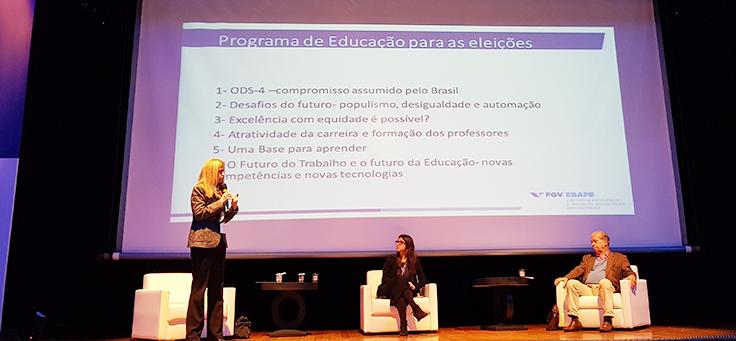 Claudia Costin, coordenadora do Centro de Excelência e Inovação em Políticas Educacionais da FGV, usa paletó e está em pé palestrando no Jeduca