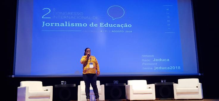 Educadora Maria do Socorro está em pé no palco do Jeduca. Ela usa blusa amarela e óculos. Está falando ao microfone sobre a vivência em escola pública