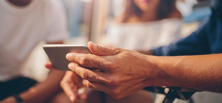 Imagem mostra mão segurando aparelho celular